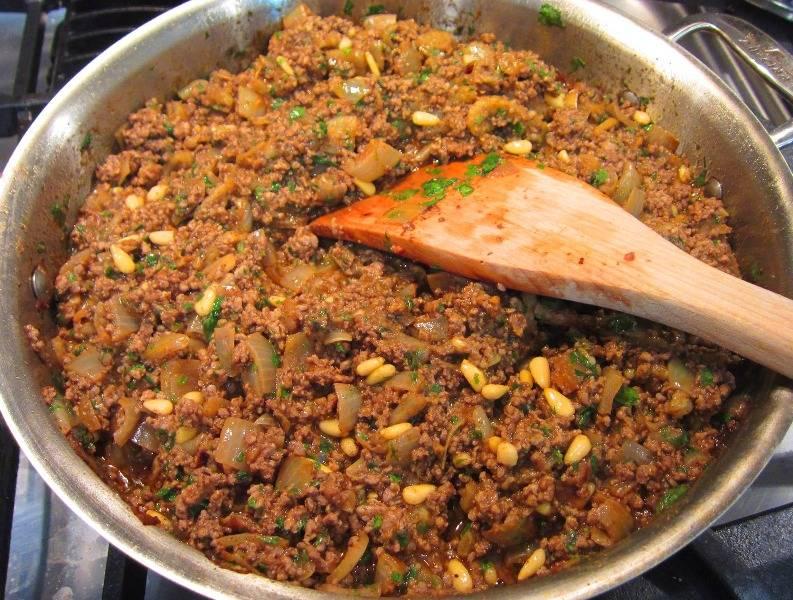 После этого добавляем к луку фарш, перемешиваем все, жарим фарш до золотистого цвета. В конце добавляем кедровые орехи, лимонный сок, томатную пасту, сахар, тамаринд, соль и перец по вкусу. Еще раз перемешиваем все, жарим фарш с луком 2 минуты, а затем снимаем сковороду с огня и добавляем в начинку петрушку.