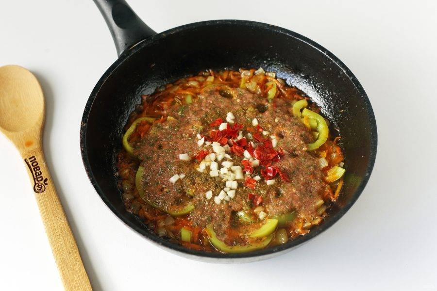 Готовьте все вместе около 5 минут, после чего добавьте томатный соус, измельченный чеснок и мелко нарезанный острый перец.