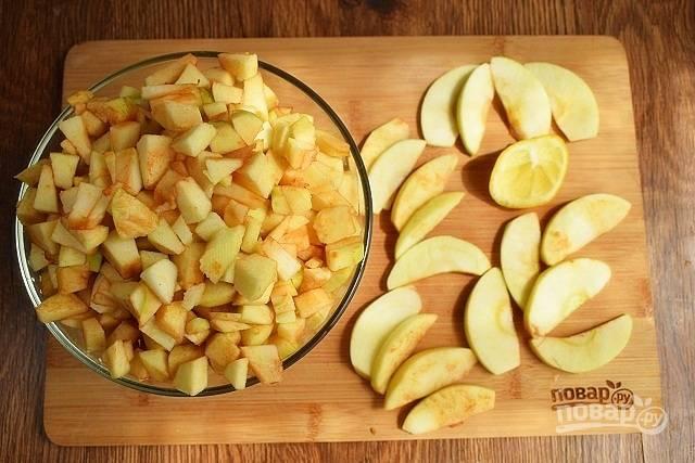 Включите духовку на 180 °C, она должна хорошо прогреться. Яблоки очистите и удалите сердцевину. Нарежьте все яблоки, кроме одного, на  кубики по 0,5 см. Одно яблоко нарежьте тонкими дольками. Брызните на яблоки лимонным соком.