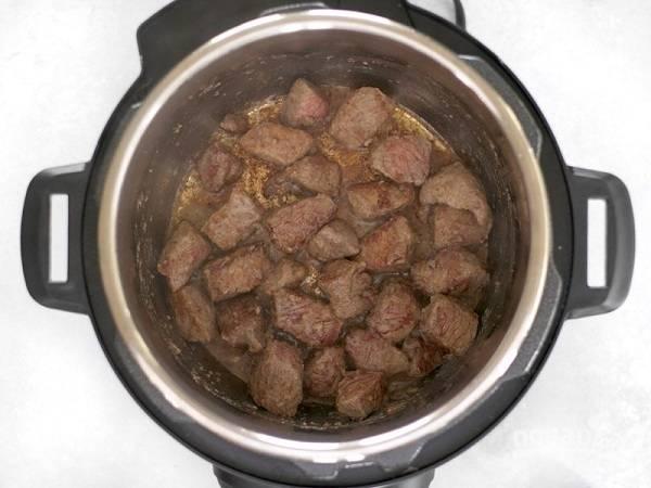 2. В чаше мультиварки на режиме Жарка растопите сливочное масло и обжарьте до образования корочки говядину.