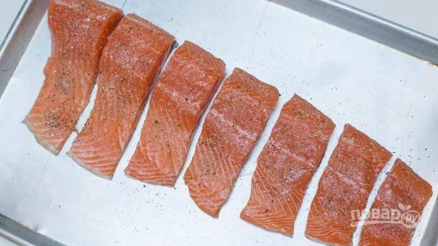 2. Нарежьте порционными кусочками и выложите на противень. Посолите и поперчите по вкусу, по желанию добавьте специи для рыбы. Полейте соком лимона.