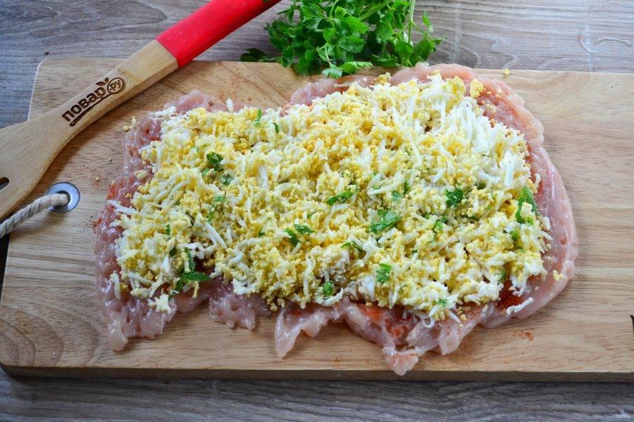 Полученный пласт куриного мяса посолите, присыпьте перцем и паприкой. Затем выложите подготовленную начинку достаточно толстым слоем.