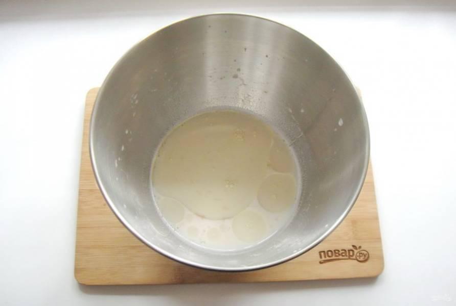 Приготовьте тесто. Для этого воду смешайте с молоком и подогрейте. Добавьте дрожжи, сахар, 3-4 столовые ложки рафинированного подсолнечного масла и соль. Я смешивала все ингредиенты в чаше миксера, но можно это сделать в любой глубокой посуде.