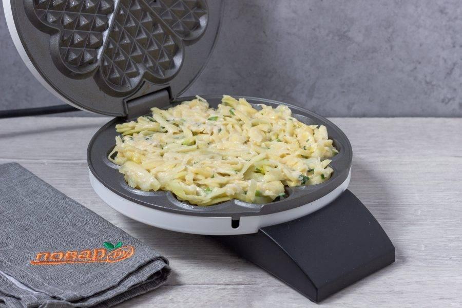 Вафельницу нагрейте. С помощью силиконовой кисти смазывайте растительным маслом перед каждым драником. Выложите картофельную массу на всю поверхность и готовьте как обычные вафли - по индикатору.