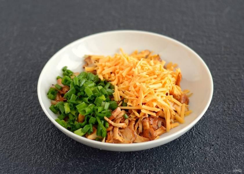 Переложите лисички в миску, добавьте тертый сыр и нарезанный зелёный лук.