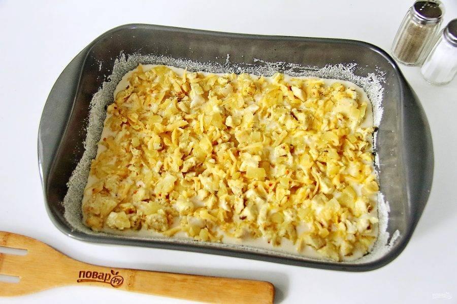 Форму для выпечки смажьте маслом, дно и бока обсыпьте манкой или сухарями и вылейте примерно половину порции теста. Сверху равномерно разложите начинку.