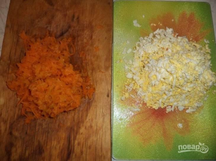 1.Отварите морковку до готовности, затем измельчите её на терке. В отдельной кастрюле приготовьте яйца, остудите их и натрите на крупной терке.