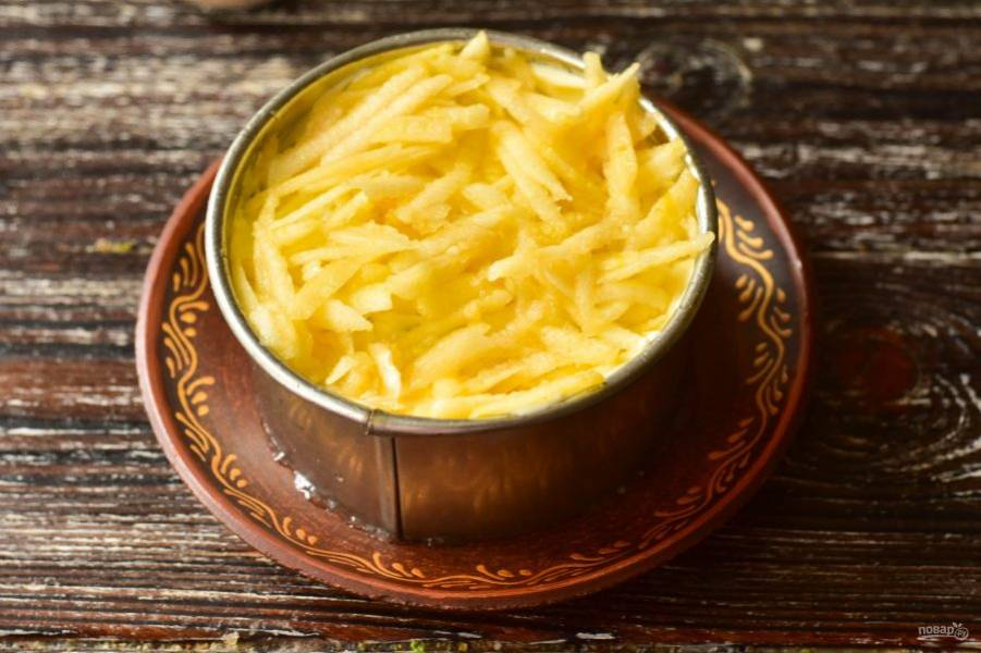 Смажьте картофель майонезом, выложите тертое на крупной терке яблоко, которое предварительно очистите от кожуры.