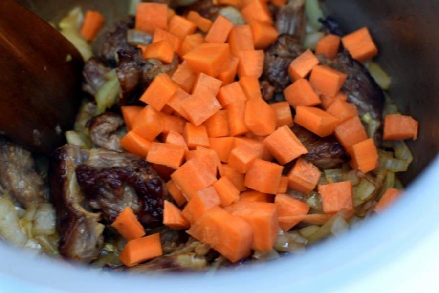 Морковь нарежьте крупными кубиками и добавьте к мясу. Слегка обжарьте.