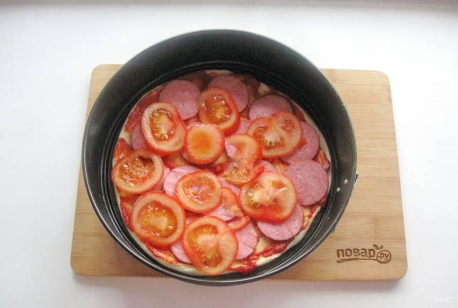Помидоры нарежьте и выложите на колбасу. Отправьте пиццу в духовку разогретую до 175-180 градусов на 25-30 минут. Время выпекания зависит от вашей духовки.