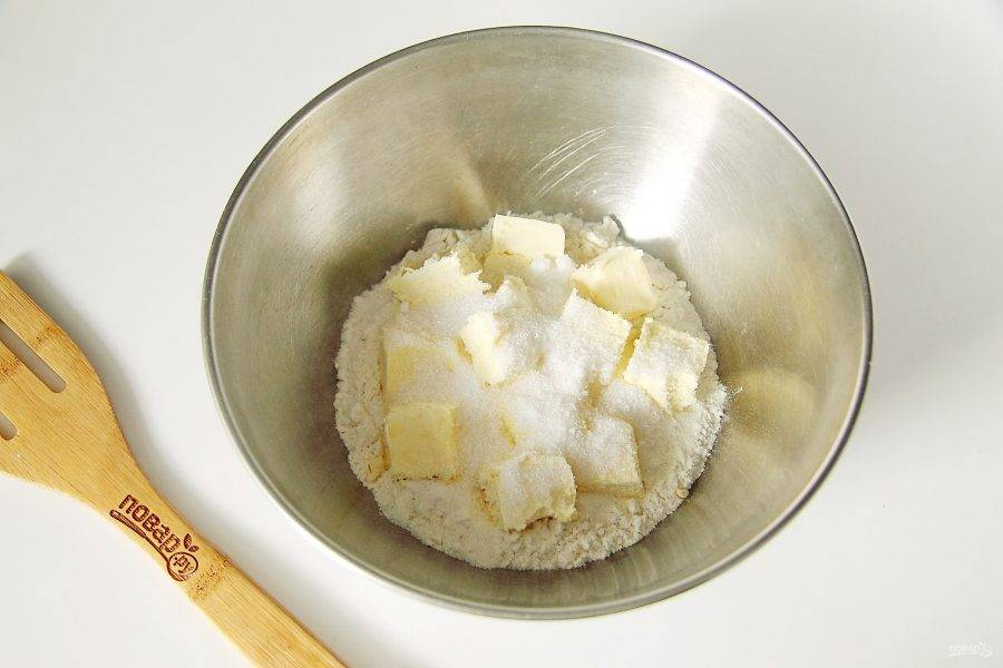 В глубокую миску насыпьте муку, добавьте нарезанное кубиками масло, соль и 1 ст.л. сахара.