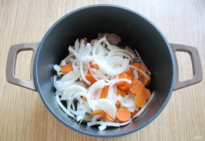 Морковь и репчатый лук очистите, помойте и нарежьте. Лук я нарезала полукольцами, а морковь – кружками. Добавьте к мясу в кастрюлю.