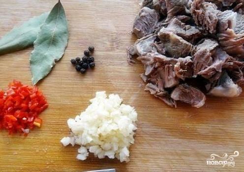 Мясо отделяем от кости и нарезаем. Мелко-мелко порежем перчик чили и очищенные зубчики чеснока.