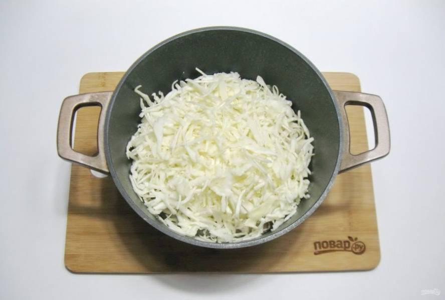 Когда свинина будет практически готова, добавьте в кастрюлю нарезанную капусту.