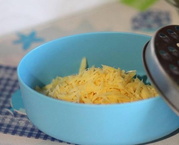 4. Натереть на средней терке твердый сыр. В рецепт приготовления салата из копченой грудки можно использовать абсолютно любой сыр, который есть в холодильнике. Подойдет также моцарелла или брынза, например.