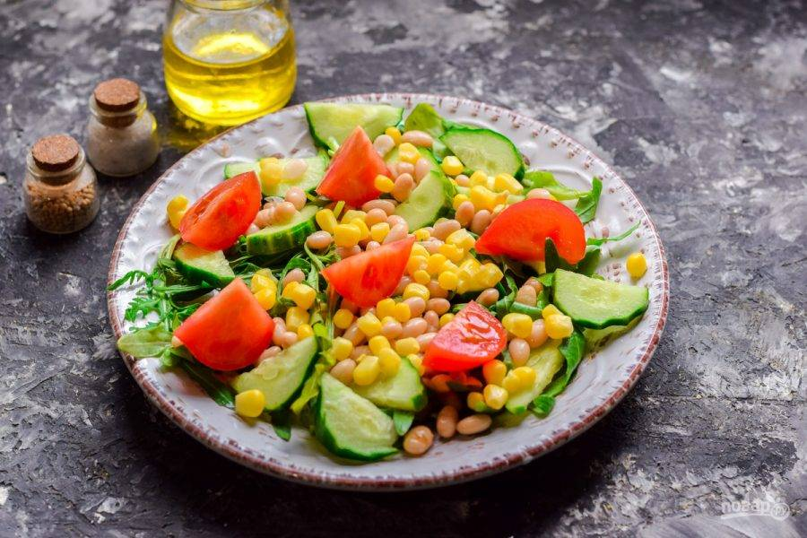 Помидор сполосните и просушите, нарежьте томат дольками и переложите в салат. Заправьте салат маслом, добавьте лимонный сок, соль и перец.