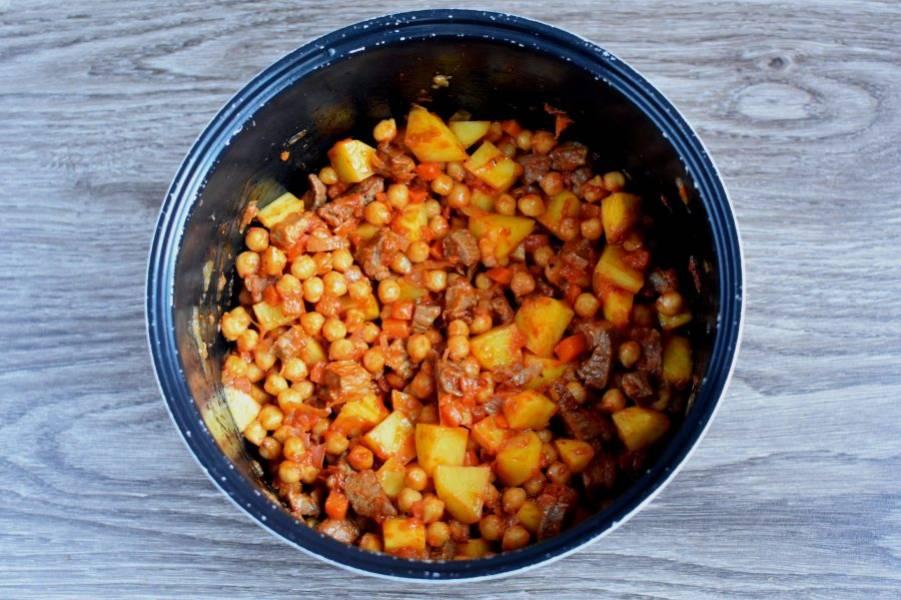 Выложите картофель кубиками и добавьте томатную пасту. Обжарьте все вместе еще 7-8 минут, помешивая.