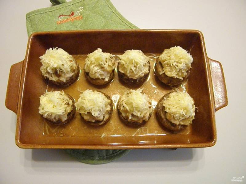 Теперь достаньте шампиньоны, посыпьте щедро с горкой тертым сыром и отправьте в духовку еще на 5 минут, чтобы расплавился сыр.