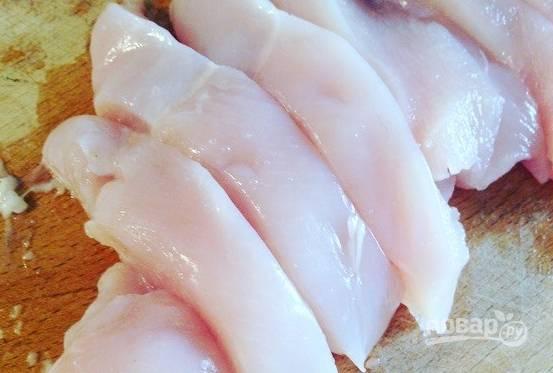 Куриное филе вымойте и зачистите от пленок. Затем разрежьте курочку на продолговатые кусочки.
