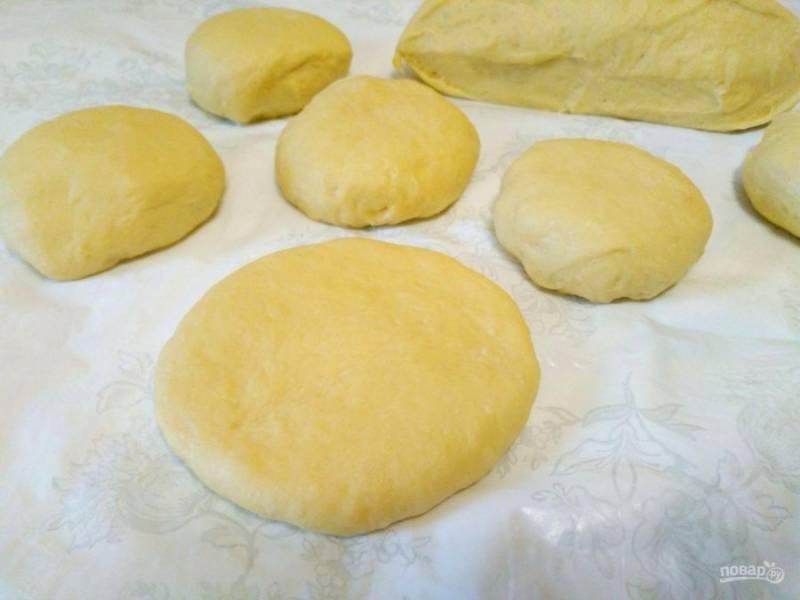 Разделите тесто на 12-14 кусочков и сформируйте из них шарики, а затем поочерёдно раскатайте каждый в лепёшку толщиной примерно в 1 сантиметр.