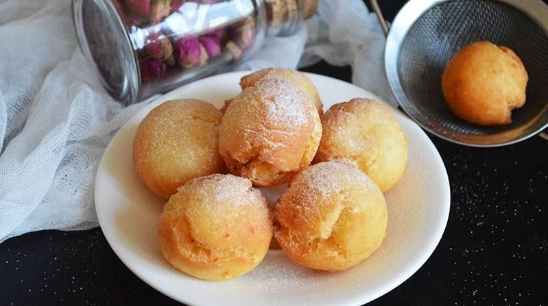6. Пончики аккуратно достаньте шумовкой и выложите на салфетку. Удалите остатки масла. Можно подавать пончики к столу, посыпав их сахарной пудрой или корицей, например.