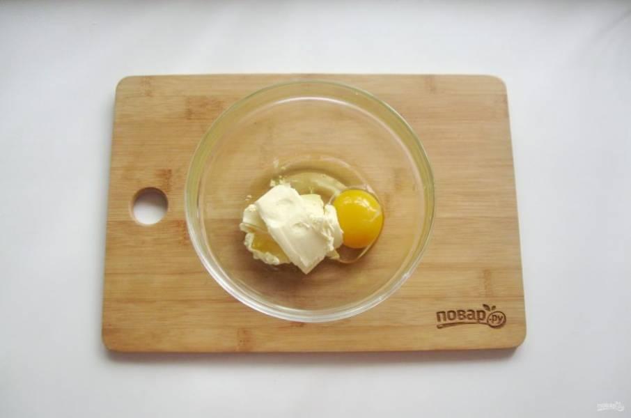 Приготовьте тесто. В миску выложите мягкое сливочное масло и добавьте яйцо.