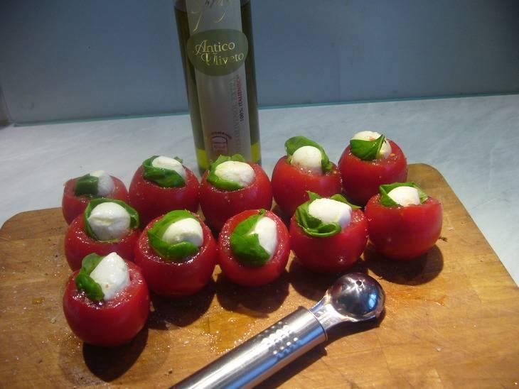 Сливаем с моцареллы рассол. Разрезаем ее на несколько кусочков и каждый кусочек оборачиваем в лист базилика. Фаршируем сыром помидоры.