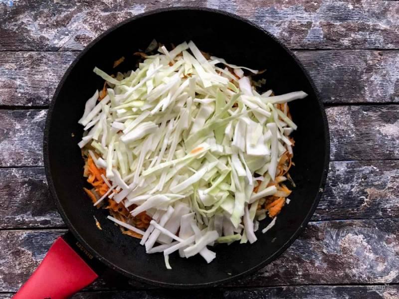 К луку с морковью добавьте половину мелко нарезанной капусты, хорошо перемешайте и тушите 15 минут под закрытой крышкой.