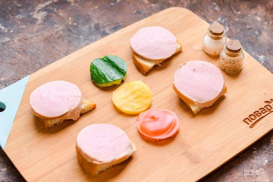 Вареную колбасу нарежьте небольшими кружочками, выложите поверх хлеба.