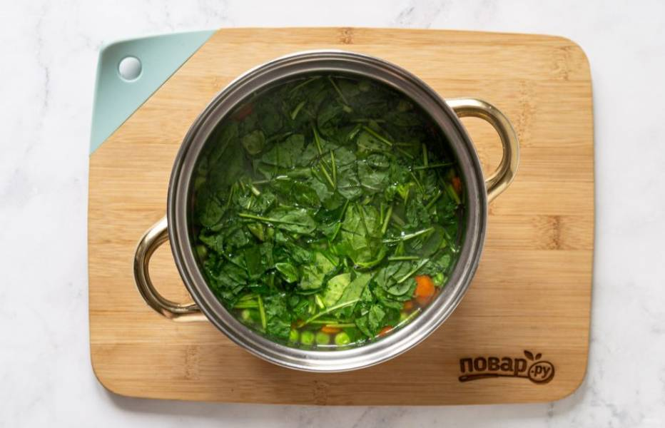 Добавьте шпинат в кастрюлю, варите суп еще 5 минут.
