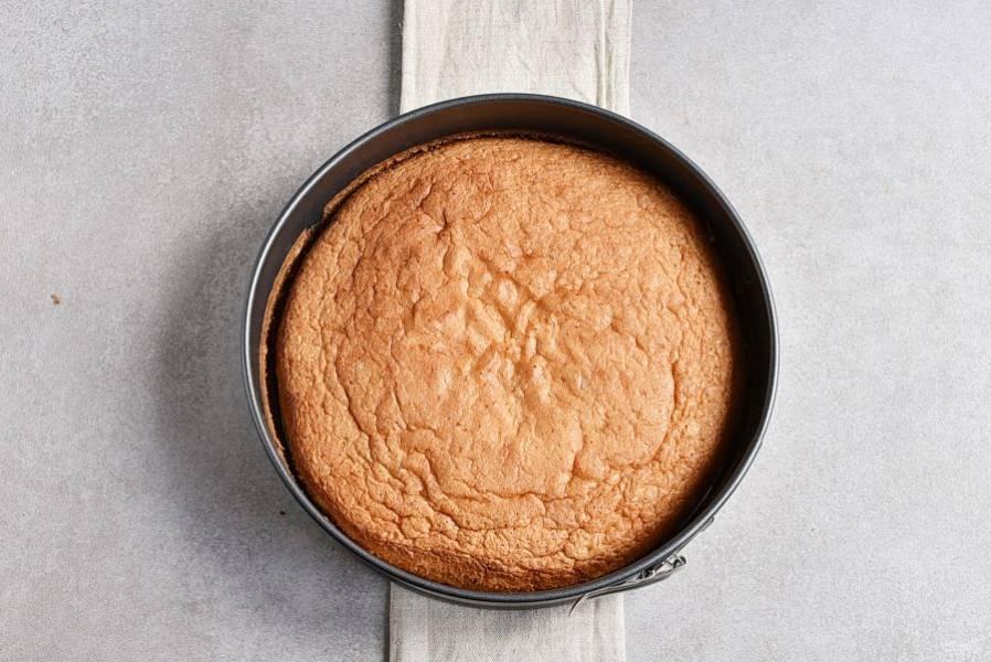 Выпекайте минут 20, проверьте готовность бисквита шпажкой. Готовому бисквиту дайте немного остыть в форме. Затем извлеките, подрезав края.