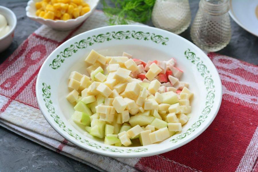 Нарежьте кубиками плавленый сыр и добавьте в салат.