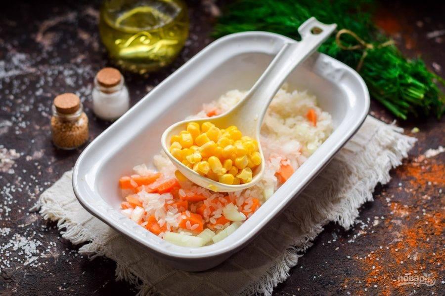 Рис промойте и сложите в форму для запекания. Добавьте к рису морковь и лук, перемешайте, добавьте кукурузу.