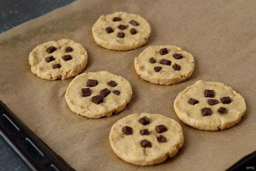 Сформируйте из теста печенье, выложите его на пергамент. Сверху добавьте порезанный на маленькие квадратики шоколад. Выпекайте печенье в духовке 12-15 минут при температуре 190 градусов.