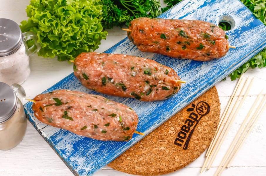 Затем из части фарша сформируйте округлую котлету и проткните ее шампуром: металлическим или деревянным. Сожмите в ладони мясо, чтобы оно прочно основалось на шампуре.