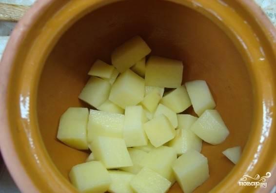 Выкладываем нарезанный картофель на дно каждого горшочка.
