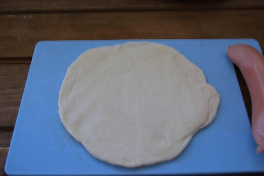 Разделите тесто на небольшие кусочки. Каждый кусочек раскатайте в пласт. На край пласта выложите очищенную сосиску. Накрутите тесто на сосиску.