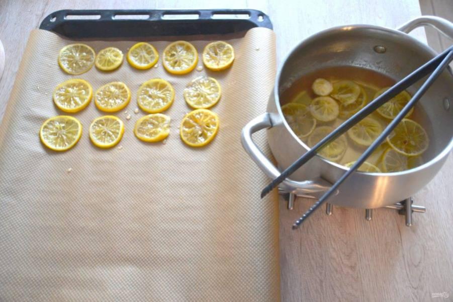 Кулинарными щипцами или просто вилкой выложите лимонные ломтики на бумагу для выпечки.