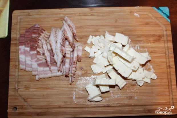 В это время нарежьте бекон средними кусочками, а плавленый сыр — мелкими кубиками. Вкиньте его к картофелю за 5 минут до готовности.