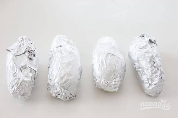 1. Картофель вымойте, обсушите и по отдельности заверните в фольгу. Отправьте в разогретую до 200 градусов духовку и запекайте минут 50-55 до мягкости (готовность можно проверить зубочисткой).