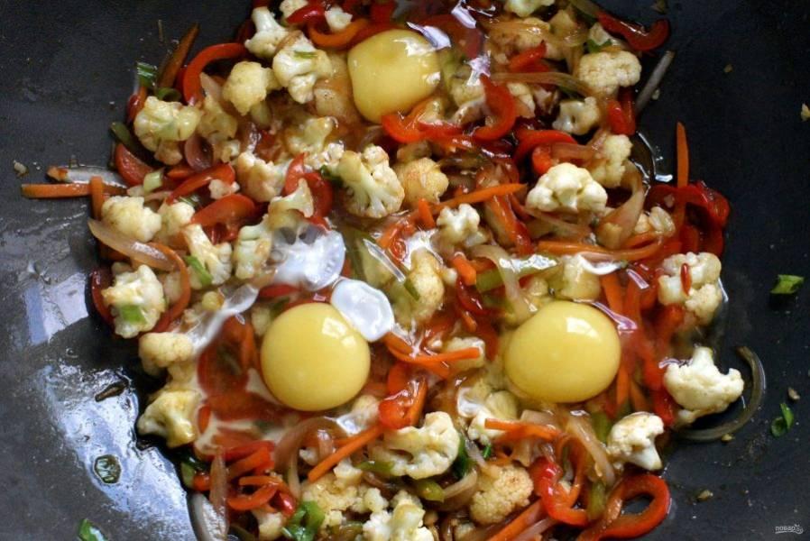 Разбейте в овощи яйца.