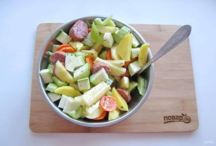 Влейте оливковое масло с приправой в смесь овощей с колбасками, посолите и перемешайте.