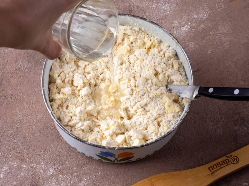 Подготовьте воду. Небольшими порциями вливайте в тесто и рубите. Воды может уйти от полстакана и больше. Ориентируйтесь на свертываемость теста. Подливайте и рубите.