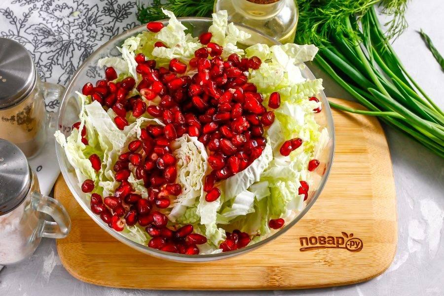 Гранат аккуратно разрежьте пополам и счистите семена в емкость к капустной нарезке. Можно выбрать как сладкий, так и кисловатый фрукт — он в любом случае будет идеален для блюда.