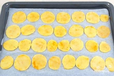 3. Разогрейте духовку, установив температуру 200 градусов. Застелите противень пекарской бумагой. Смажьте маслом. Переложите заготовку для чипсов на бумагу для выпечки. Чипсы подсушатся в течение 15-20 минут.