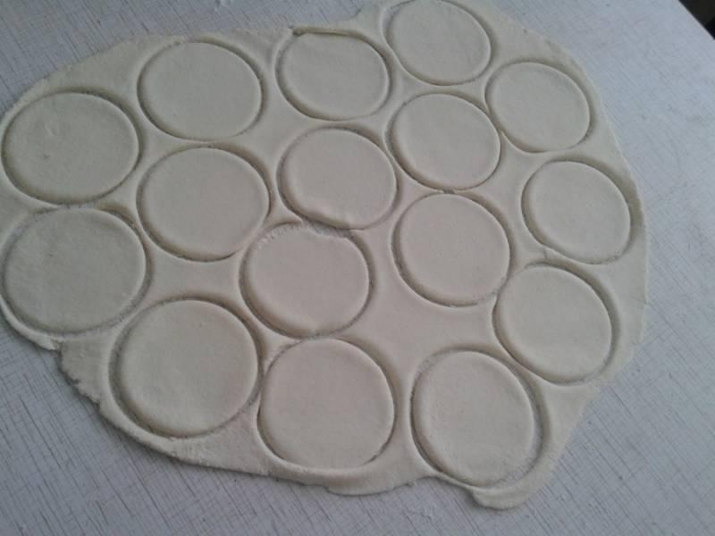 При помощью формочки или стакана вырежьте из теста кружочки. Выложите в центр каждого чайную ложку сгущенки.  Слепите из теста с начинкой овалы, слегка приплюснув по бокам.