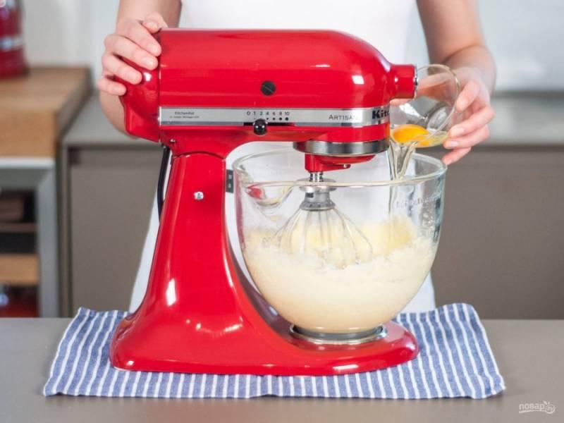 Затем в масляную массу добавьте яйца. Взбейте смесь до единой консистенции.