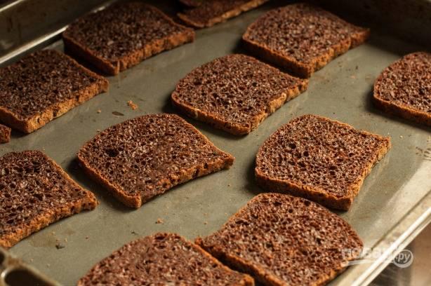 Нарезаем хлеб на ломтики и подсушиваем в духовке. Можно даже слегка пересушить, чтобы на некоторых кусочках образовалась очень темная корочка.