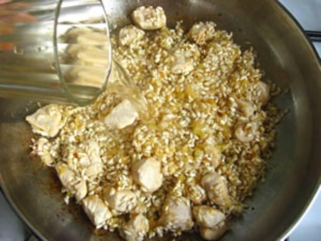 Влейте вино и оставьте на пару минут, чтобы вино немного испарилось, затем влейте четверть бульона и готовьте помешивая пока рис не впитает почти всю жидкость.