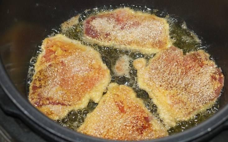 """В мультиварке включите режим """"Жарка"""", налейте в кастрюлю растительное масло. Ромштексы обмакните сначала в яйцо, затем — в сухари. Когда растительное масло нагреется, выкладывайте жарить ромштексы."""